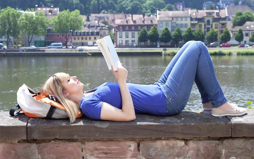 Mulher ralaxando lendo um livro.