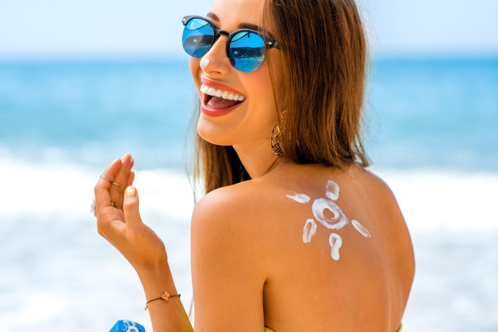 Mulher com creme de sol na praia