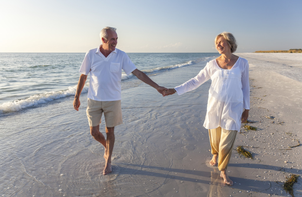 Happy Senior Couple Walking Holding Hands Tropical Beach
